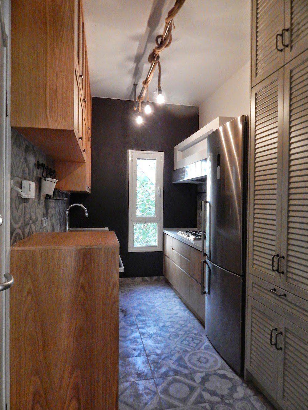 Μια στενόμακρη κουζίνα, χωριστό δωμάτιο αλλά πέρασμα ταυτοχρόνως διαφοροποιείται και δεν είναι βαρετή αφού αποκτά ύφος παλιού παντοπωλείου. Στην μία πλευρά αναπτύσσεται ένα σύστημα πάγκου εργασίας και ερμαρίων με γυάλινες όψεις, ενώ απέναντι η θέση μαγειρέματος διαθέτει όλα τα απαραίτητα για τη διαδικασία αλλά και μια κατασκευή παλιάς χωριάτικης όψης. Στα δεξιά μια μεγάλη τροφοθήκη με πόρτες γρίλια κρύβει αποθηκευτικούς χώρους αλλά και πρόχειρο τραπέζι φαγητού!